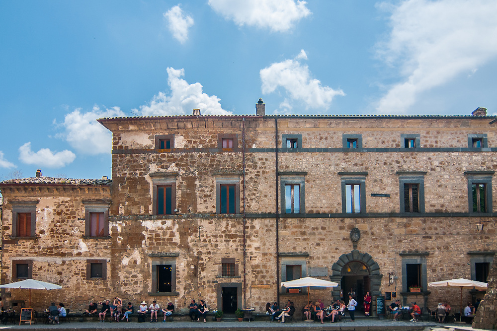 Tourists enjoy a sunny day in San Donato square in Civita di Bagnoregio.<br /> Civita di Bagnoregio is a town in the Province of Viterbo in central Italy, a suburb of the comune of Bagnoregio, 1 kilometre (0.6 mi) east from it. It is about 120 kilometres (75 mi) north of Rome. Civita was founded by Etruscans more than 2,500 years ago. Bagnoregio continues as a small but prosperous town, while Civita became known in Italian as La citt&agrave; che muore (&quot;The Dying Town&quot;). Civita has only recently been experiencing a tourist revival. The population today varies from about 7 people in winter to more than 100 in summer.The town was placed on the World Monuments Fund's 2006 Watch List of the 100 Most Endangered Sites, because of threats it faces from erosion and unregulated tourism.