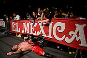 Lucha Libre AAA wrestler Jack Evans recovers from being thrown out of the ring in San Jose, CA March 29, 2009.