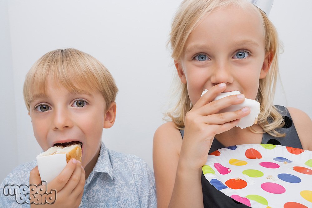 Portrait of cute siblings eating birthday cake slices in house