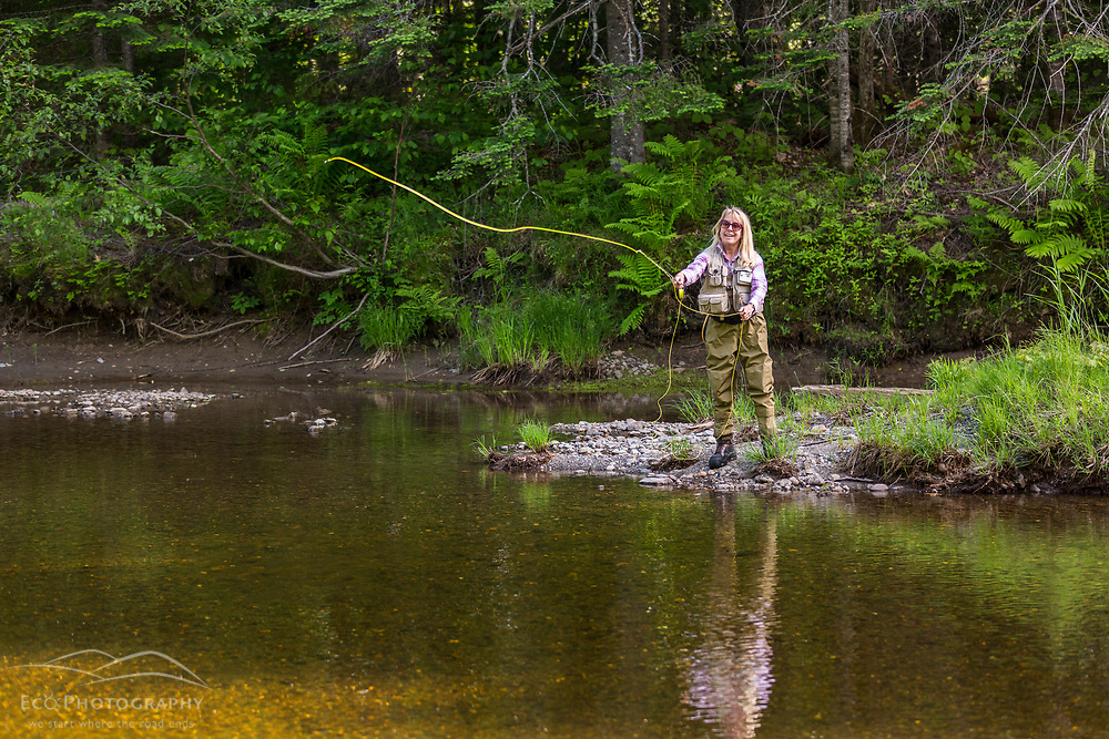 A woman fly-fishing on the West Branch of the Pleasant River near Silver Lake in Piscataquis County, Maine. Near Greenville.