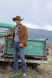 rugged and handsome cowboy outdoors cowboy leaning on a vintage truck in the mountains
