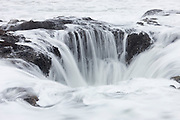 Pacific Ocean waves flow into the remnants of a blowhole at Cape Perpetua on the Oregon coast. Blowholes are essentially skylights in ocean caves. At high tide, water fills the cave and the pressure of the incoming waves forces water through the hole, high into the air. Over time, erosion has enlarged this hole so that water no longer jets out of it, though it does make a dramatic 360-degree waterfall.