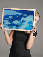 Young businesswoman peeking from behind a photograph of cruise ship on water against gray background