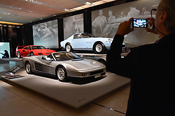 "© Licensed to London News Pictures. 14/11/2017. London, UK.  A visitor photographs (front to back) A Ferrari Testarossa Spyder, 1986, commissioned by Gianni Agnelli to commemorate his 20th anniversary as Chairman of Fiat, a Ferrari 275 GTB/4, 1967, and a Ferrari F40, 1987, built to celebrate the 40th anniversary of Ferrari.  Preview of ""Ferrari: Under the Skin"", an exhibition at the Design Museum to mark the 70th anniversary of Ferrari.  Over GBP140m worth of Ferraris are on display from private collections including Michael Schumacher's 2000 F1 winning car.  The exhibition runs 15 November to 15 April 2018.  Photo credit: Stephen Chung/LNP"