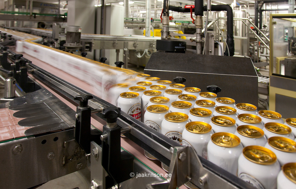 Large numbers of beer cans, moving along a conveyor belt in the production process. Packaging and production. Ring pull cans. Branded.