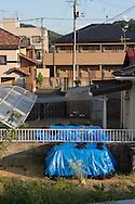 Trädgårdar i vars översta strålningskadade jordlager är samlat under blå pressening i ett bostadsområde i Fukushima City, Japan