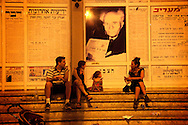 Israeli protestors taking a break on the stairs of the national press house, under a portrait of David Ben-Gurion, the first Israeli prime minister, during the massive demonstration over the rising cost of living in the country.  Tel-Aviv, Aug. 6, 2011. <br /> <br /> At least a courter of million Israelis marched in a protest against the rising cost of living in Israel, in central Tel Aviv, Saturday, Aug. 6, 2011. The Israeli citizens are furious over the worsening social conditions in the country due to the increasing pricing of housing, taxes and basic products and also protesting over the lack of social welfare. Israelis poured en masse into the streets of major cities on Saturday night in a massive demonstration. Thousands of mostly middle class Israelis marched through the streets of the city waving flags, beating drums and shouting: &quot;The people demand social justice&quot;.