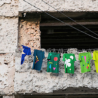 MOSTAR, BOSNIA AND HERZEGOVINA - JUNE 28:  Line drying shirts are seen in front of a concrete wall damaged by bulletts from the 1993 war is seen on June 28, 2013 in Mostar, Bosnia and Herzegovina. The Siege of Mostar reached its peak and more cruent time during 1993. Initially, it involved the Croatian Defence Council (HVO) and the 4th Corps of the ARBiH fighting against the Yugoslav People's Army (JNA) later Croats and Muslim Bosnian began to fight amongst each other, it ended with Bosnia and Herzegovina declaring independence from Yugoslavia.  (Photo by Marco Secchi/Getty Images)