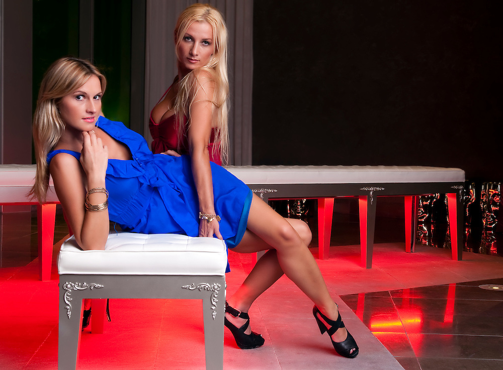 Girlfriends in a modern lounge with sensual pose.
