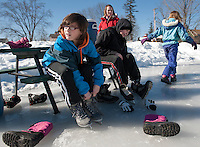 Sierra Shaw and Patrick Duggan lace up their skates at Memorial Park for Laconia Parks and Recreations skating party on Friday afternoon.  (Karen Bobotas/for the Laconia Daily Sun)