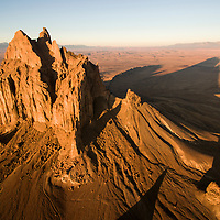 USA, New Mexico, Shiprock, Aerial view of jagged summit of Ship Rock at sunrise rising nearly 1,583 feet (482.5 m) above the high-desert plain of the Navajo Nation in San Juan County