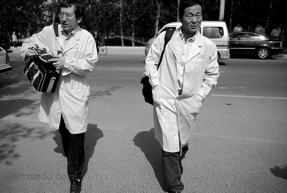 Chinese doctors walk outside of the hospital where a group of vehicles, including ambulances from the Beijing Emergency Medical Center carrying Mexican nationals, leave the sealed-off Guomen Hotel where they were being held under quarantine for Beijing airport, May 5, 2009. Mexico announced plans on Monday to send a plane to retrieve dozens of its nationals confined across China, which quarantined them as a protective measure against a deadly new strain of flu