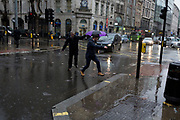 Storm Georgina swept across parts of Britain and in central London, lunchtime office workers were caught out by torrential rain and high winds, on 24th January 2018, in London, England. Pedestrians resorted to leaping across deep puddles at the junction of New Oxford Street and Kingsway at Holborn, the result of overflowing drains. Second in a sequence of seven photos.