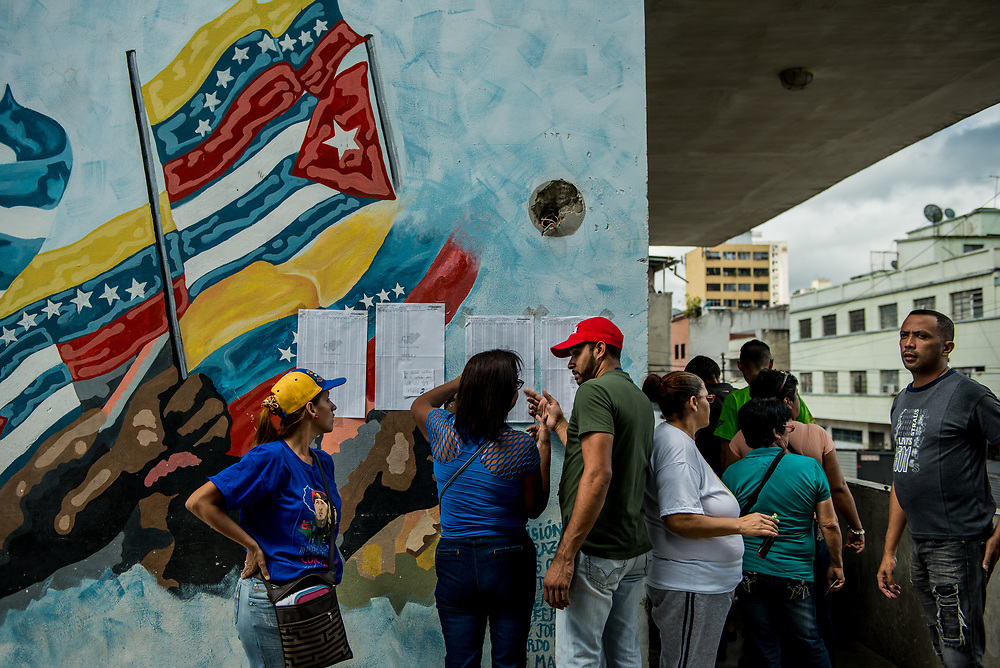 CARACAS, VENEZUELA - JULY 30, 2017:  Government supporters check an election registry taped to a mural painted with Venezuelan and Cuban flags, to see which polling table to cast their votes at. Many fear this election will turn Venezuela similar to Cuba. Opponents of the government criticize President Maduro for calling for this election - saying the new assembly is a power grab, and will be a puppet of the President - the only candidates on the ballot are government loyalists. Critics also fear the new assembly will turn the country into a dictatorship, re-write the constitution and wipe out the democratically elected and opposition controlled congress. There have been widespread reports of voter intimidation, and of the government threatening state workers and citizens that receive government benefits like subsidized food - who report the government telling them they are obligated to vote, and if they don't, they will lose their jobs and benefits. Thousands have taken to the streets to protest the election in the days leading up to the July 30th vote.  PHOTO: Meridith Kohut for The New York Times
