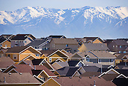 Rooftops of urban sprawl are set against a backdrop of majestic mountains in the distance.