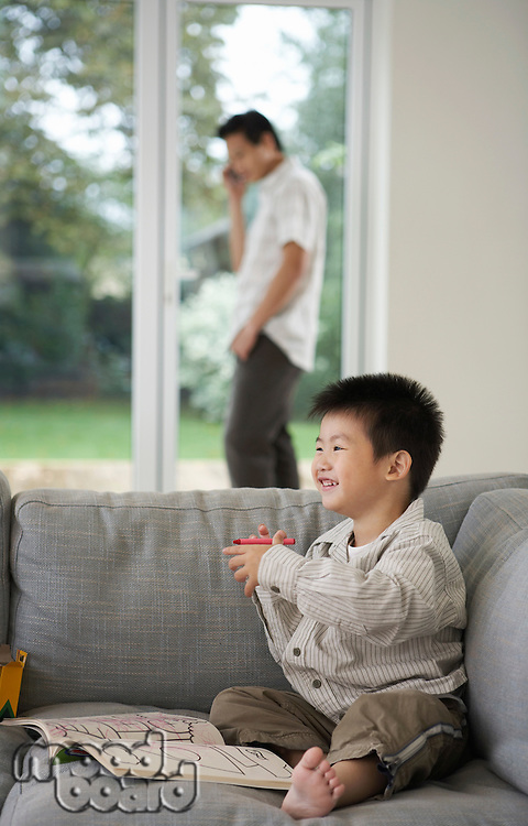 Smiling Boy on sitting barefooted on Sofa with Coloring Book father in background talking on phone