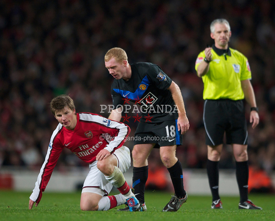 LONDON, ENGLAND - Sunday, January 31, 2010: Arsenal's Andrei Arshavin is helped off the ground by Manchester United's Paul Scholes during the Premiership match at the Emirates Stadium. (Photo by Chris Brunskill/Propaganda)