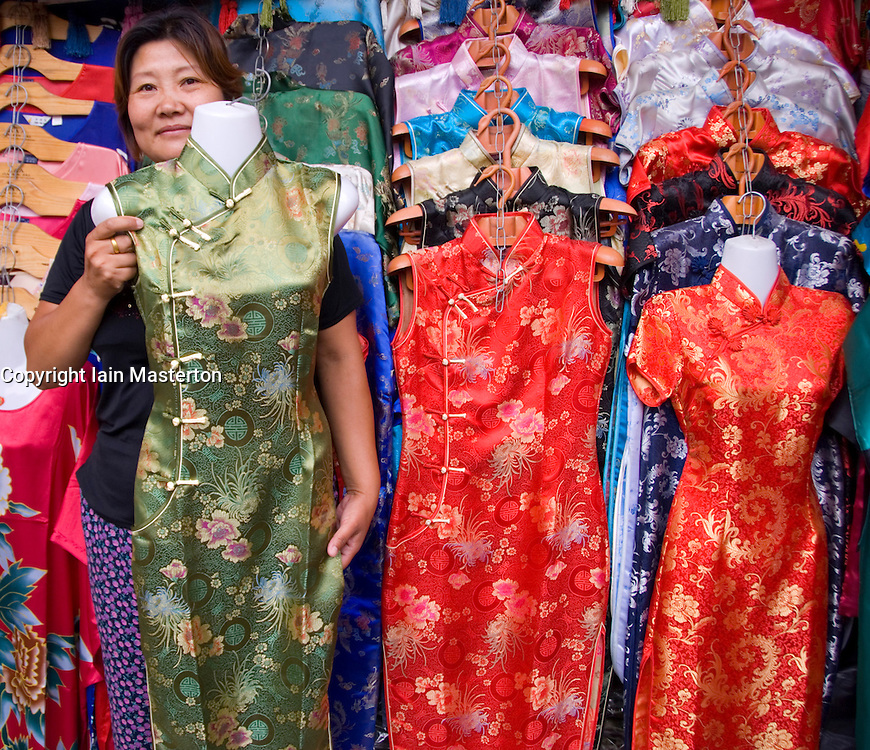 Shopkeeper displaying traditional silk ornate embroidered chongsam Chinese dress at a shop in Beijing China