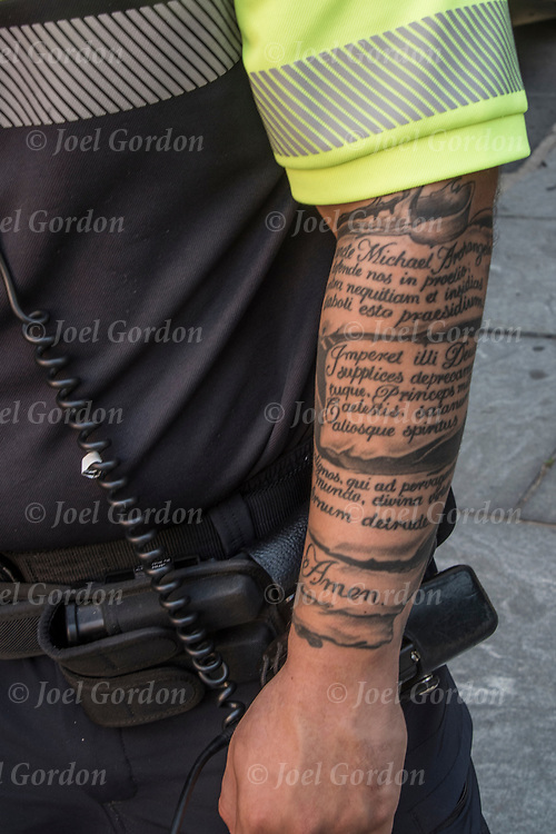 Policeman's tattoo sleeve on his lower arm showing.<br /> <br /> Body art or tattoos has entered the mainstream it is no longer considered a weird kind of subculture.<br /> <br /> &quot;According to a 2006 Pew survey, 40% of Americans between the ages of 26 and 40 have been tattooed&quot;.