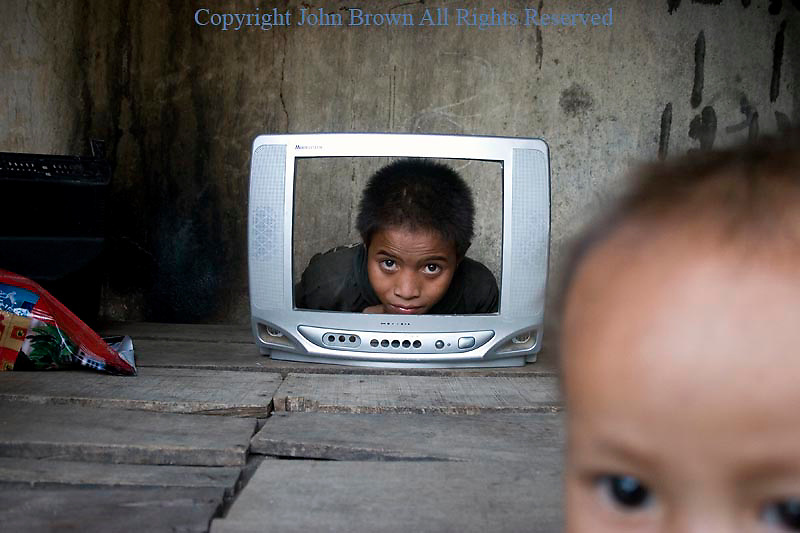 A boy is looking through the screen of a broken TV in a squatters slum in Kampong Cham, Cambodia.