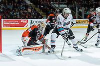 KELOWNA, CANADA - JANUARY 23: Cole Linaker #26 of Kelowna Rockets stick handles the puck in front of the net of Nick Schneider #31 of Medicine Hat Tigers on January 23, 2016 at Prospera Place in Kelowna, British Columbia, Canada.  (Photo by Marissa Baecker/Shoot the Breeze)  *** Local Caption *** Cole Linaker; Nick Schneider;