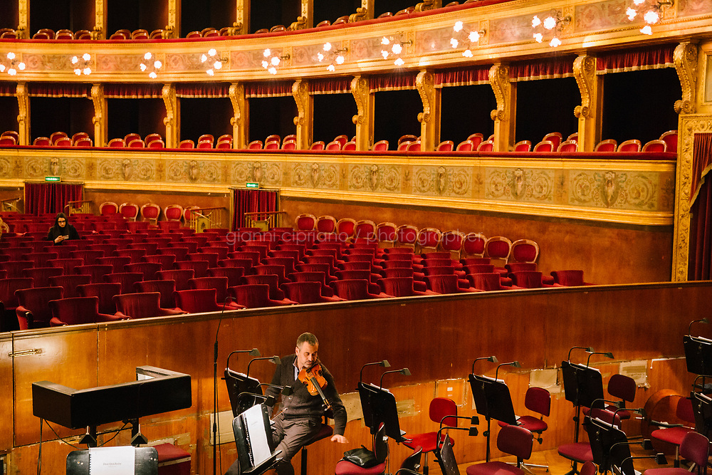 PALERMO, ITALY - 18 FEBRUARY 2018: A violinist rehearses shortly before the dress rehearsal of &quot;Don Quixote&quot; in the orchestra pit of the Teatro Massimo in Palermo, Italy, on February 18th 2018.<br /> <br /> The Teatro Massimo Vittorio Emanuele is an opera house and opera company located  in Palermo, Sicily. It was dedicated to King Victor Emanuel II. It is the biggest in Italy, and one of the largest of Europe (the third after the Op&eacute;ra National de Paris and the K. K. Hof-Opernhaus in Vienna), renowned for its perfect acoustics. It was inaugurated in 1897.