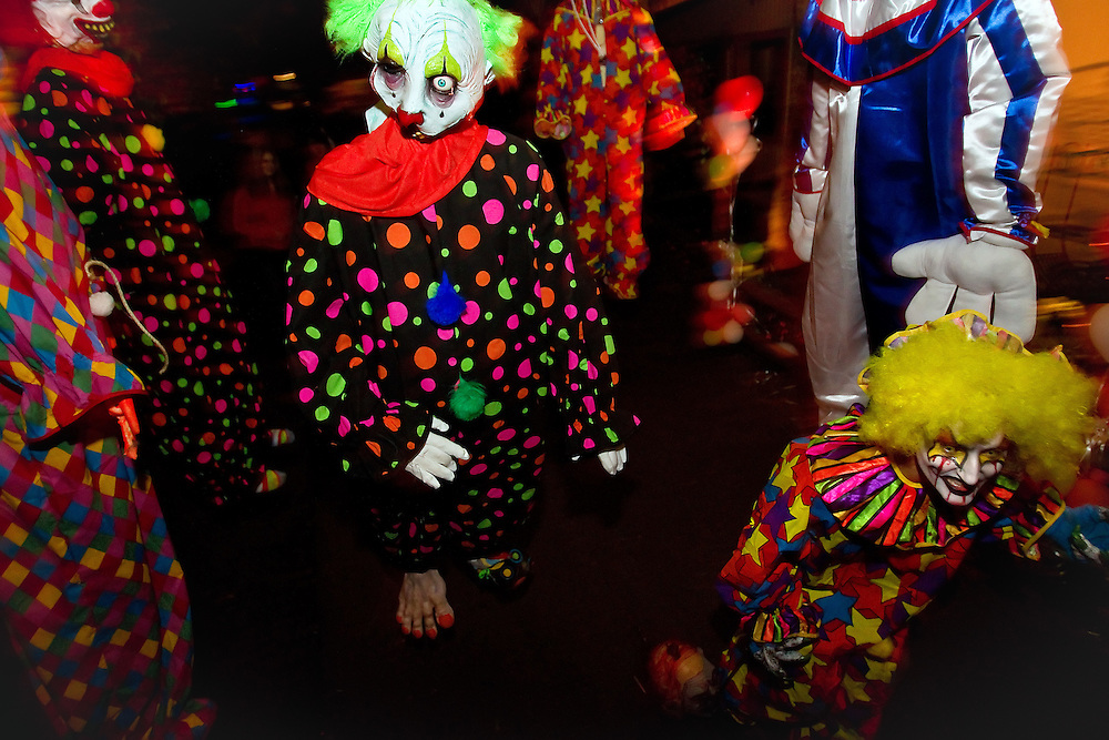 One of the creepy clowns walks through a group of his hanging companions waiting to scare Scarywood visitors.