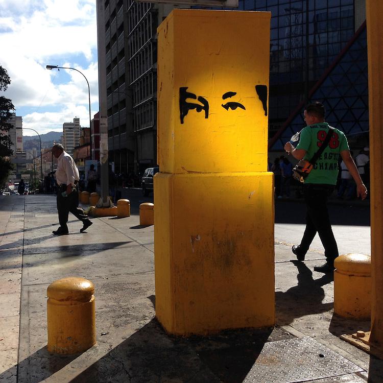 """""""Los ojos que te ven"""" es un proyecto que nació como la simple percepción de un ciudadano venezolano ante la aparición carteles con la mirada de Hugo Chávez.    La mirada de Chávez fue la imagen de su última campaña presidencial que más éxito cosechó. Miles de personas vistieron una camiseta roja -el color del chavismo- con los ojos impresos en negro. Ante la grandísima popularidad que logró, se crearon cientos de artículos que ofrecían el diseño en múltiples colores,<br /> <br /> Un año después de su muerte, esta imagen sirve ahora para recordar que Chávez sigue presente en el día a día de los venezolanos a través de su mirada, guste a quien le guste. Sus ojos, situados en cualquier lugar, parecen controlar lo que ocurre en el país.                          AFP PHOTO/ LEO RAMIREZ"""