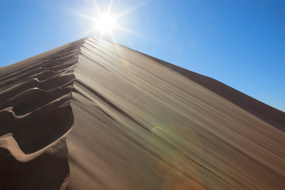 Sahara desert sand dunes with footprints against clear blue sky and sun at Erg Chebbi, Merzouga, Morocco.