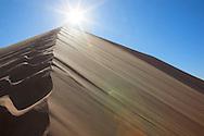 Sahara desert sand dunes with footprints against clear blue sky and sun at Erg Chebbi, Merzouga, Morocco.