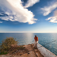 Fisherman on the top of a cliff, town of Porches, municipality of Lagoa, district of Faro, region of Algarve, Portugal