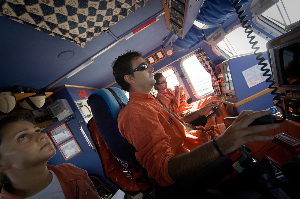 Coastguard members are seen during a rescue mission at the controls of Salvamar Alphard boat. The cayuco was intercepted 80 miles away from the coast of Tenerife, in the Canary Islands, Spain, Wednesday, Oct. 24, 2007.