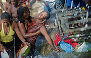 A woman pran lwa - catches the spirit - while worshipping beneath the falls at Saut D'eau in central Haiti during the annual voodou festival held there in July. In such instances the voodooist allows their body to be taken over by a specific lwa, connecting the spirit world to the physical.