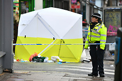 © Licensed to London News Pictures. 10/02/2019. London, UK. A police officer stands over a tent covering the body, at the scene on Lordship Lane in East Dulwich, south London where a man, believed to be in his 30's, was stabbed to death in the early hours of this morning. Photo credit: Ben Cawthra/LNP