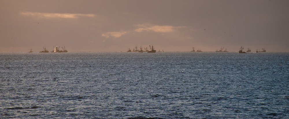 The fishing fleet of Monterey operates in the bay at sunset on a stormy May evening