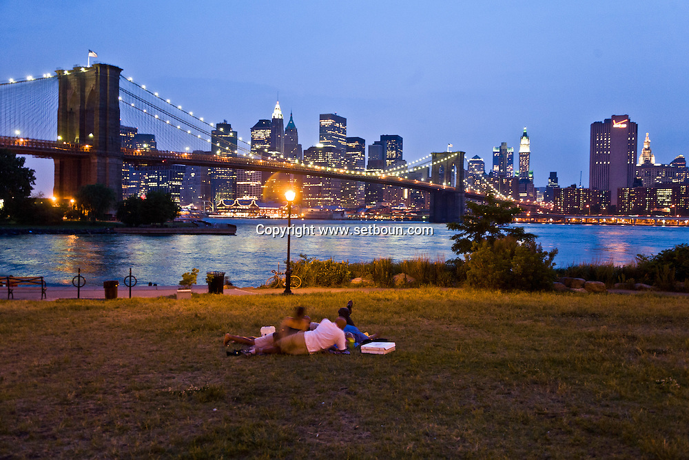 New York. Brooklyn. People watching , Manhattan cityscape  and the east river panorama , in Brooklyn bridge park,  / Brooklyn bridge parc. sous le pont de Manhattan . face au skyline des gratte-ciel de Manhattan devant l'east river   Manhattan, New York -