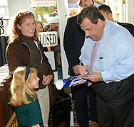 BURLINGTON CITY, NJ -  NOVEMBER 4: New Jersey Governor Chris Christie signs a campaign poster for a young girl while campaigning at Old City Quilts November 4, 2013 in Burlington City, New Jersey. Republican Governor Chris Christie faces Democratic state senator Barbara Buono in the November 5th general election. (Photo by William Thomas Cain/Cain Images)