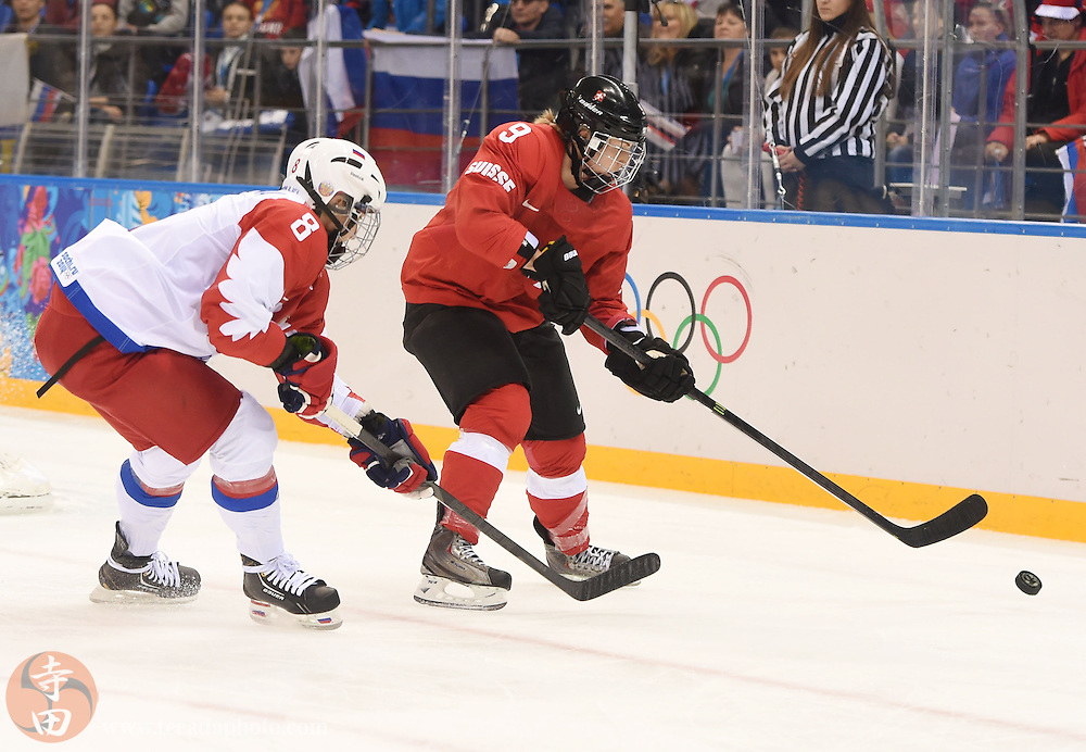 Feb 15, 2014; Sochi, RUSSIA; Switzerland forward Stefanie Marty (9) skates with the puck as Russia forward Iya Gavrilova (8) defends in a women's quarterfinals ice hockey game during the Sochi 2014 Olympic Winter Games at Shayba Arena.