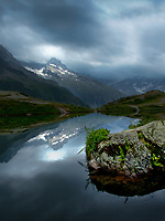 A dark, stormy day in the Southern French Alps is momentarily brightened by a brief beam of sunlight. National Parc Ecrins, France