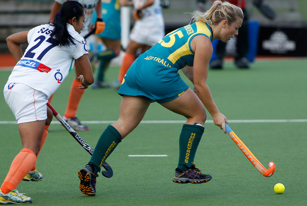 Australia's Jade Warrender, right, attempts to get past India's Sushila Pukhrambam during their four nations hockey match at North Harbour Hockey Stadium, Auckland, New Zealand, Sunday, April 15, 2012. Credit:SNPA / Ben Campbell..