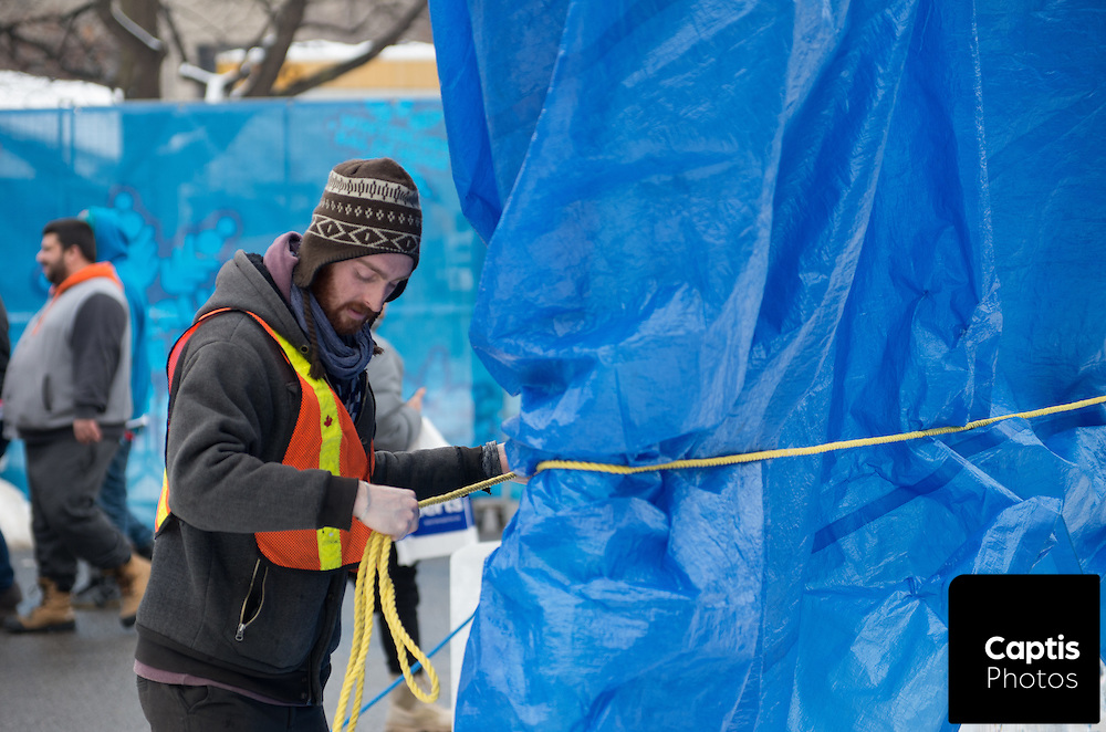 Workers cover ice sculptures with insulation and tarps as temperatures rise during Winterlude in Ottawa. January 31, 2016. Brendan Montgomery/Captis Photos