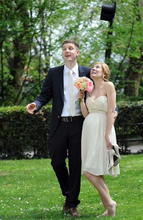 Braut und Bräutigam beobachten einen fallenden Zylinder  |     young couple on wedding day plays with a hat  |