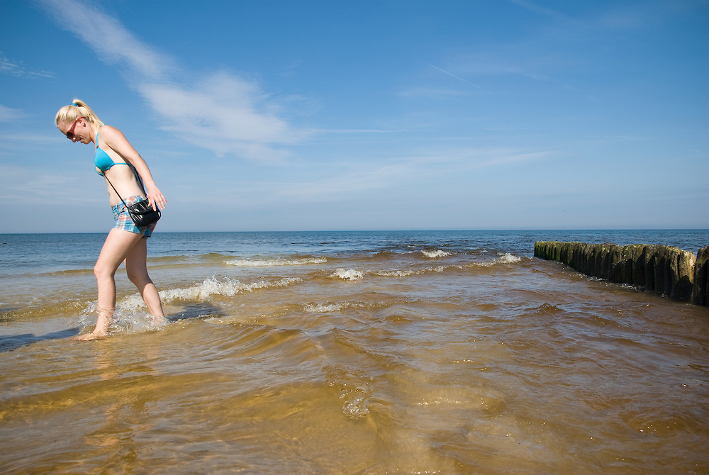 A woman paddling in the Baltic sea at Karwia, Pomorze, Poland, Sepember 2011.