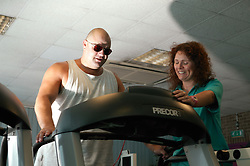Access to services, Fitness Instructor and disabled man in the gym; using Treadmill,