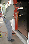 Hugh Goglin prepares the door jamb for the strikers on my new door. My old door is in the background (at left).