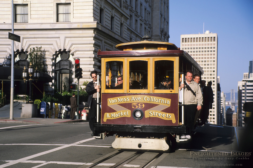 Passengers hang off the side of a Cable Car on Nob Hill, , San Francisco, California