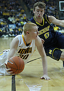January 14, 2011: Iowa Hawkeyes forward Aaron White (30) passes the ball as Michigan Wolverines guard Zack Novak (0) closes in during the NCAA basketball game between the Michigan Wolverines and the Iowa Hawkeyes at Carver-Hawkeye Arena in Iowa City, Iowa on Saturday, January 14, 2011. Iowa defeated Michigan 75-59.