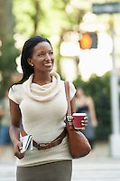 Woman with newspaper and coffee cup walking in street
