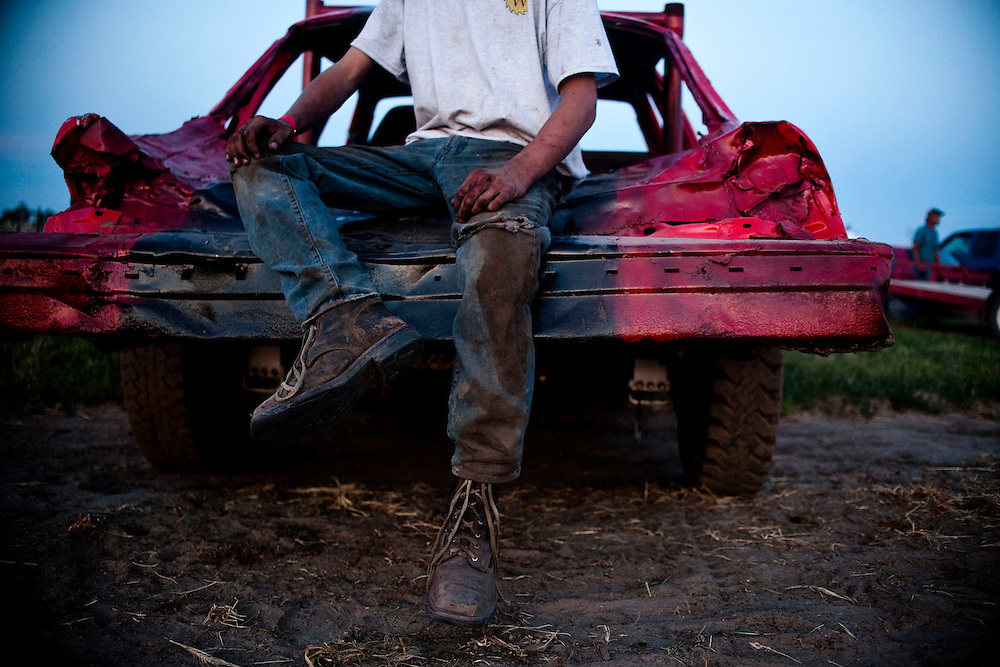 Chas Hartman, 20, sits on his car covered in sand, dirt, and grease after the demolition derby at the Fairgrounds in Valentine July 4, 2013. Photo by Lauren Justice