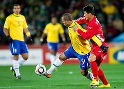 Luis Fabiano of Brazil vs Ri Kwang Chon of North Korea during the 2010 FIFA World Cup South Africa Group G match between Brazil and North Korea at Ellis Park Stadium on June 15, 2010 in Johannesburg, South Africa. Brazil defeated Korea 2-1. (Photo by Vid Ponikvar / Sportida)